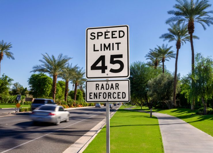 Speed Limit 45 Radar Enforced road sign with passing cars on a California street.