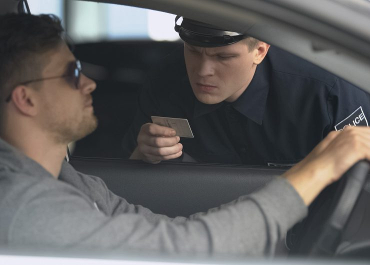 Serious policeman checking male drivers license after exceeding speed limit